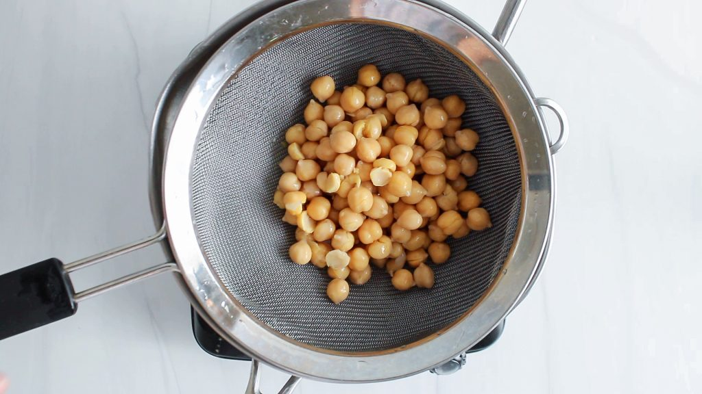In process picture: You can see some chickpeas draining in a colander into a large pot.