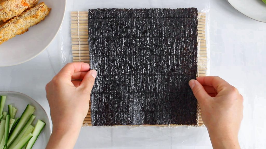 In process picture: there are 2 hands putting a nori sheet over a sushi mat