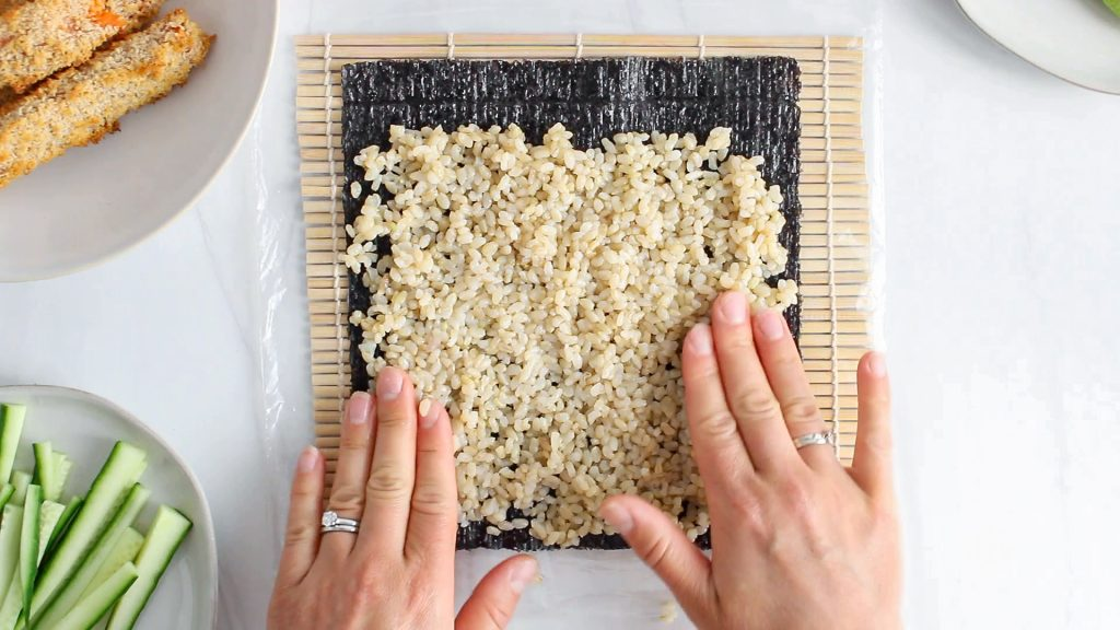 In process picture: you can see 2 hands that are pressing on brown rice over a nori sheet to make sushi rolls