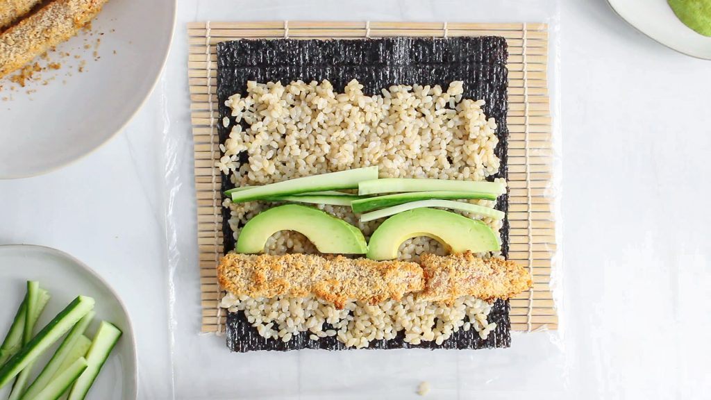In process picture: shows is a sheet of nori that's on a sushi mat and also covered with brown rice, crispy veggies, avocado and cucumber.