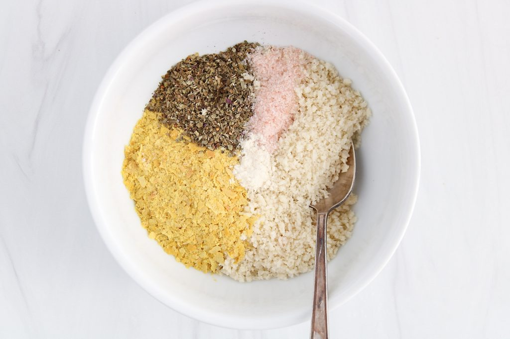 In process picture: showing is an overhead view on a small bowl containing panko breadcrumbs, nutritional yeast, salt, dried basil and garlic powder. The ingredient are placed so you can see them all.