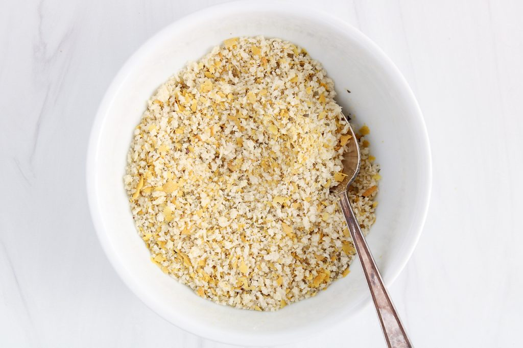In process picture: showing is an overhead view on a small bowl containing a mixture of savory panko breadcrumbs.