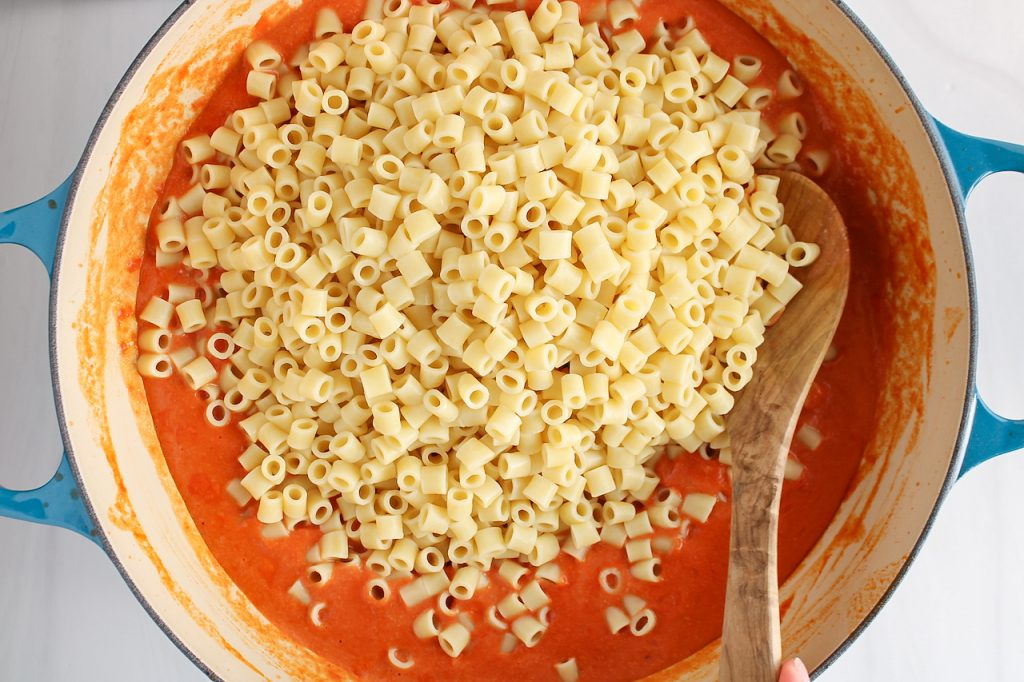 In process picture: you can see a large pan containing a red sauce that's topped with short white noodles. There is a wooden spoon just about to stir as well.