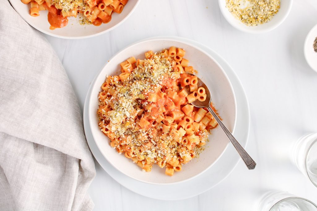 Over head view on a white bowl that contains a vegan creamy tomato pasta. The dish is topped with a crispy cheesy panko topping and there is a spoon in the bowl as well. Surrounding the bowl, you can see a small bowl with more of the panko topping, 2 glasses of water and a beige hand towel.