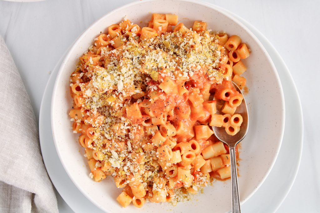 Over head view on a white bowl that contains a vegan creamy tomato pasta. The dish is topped with a crispy cheesy panko topping and there is a spoon in the bowl as well.