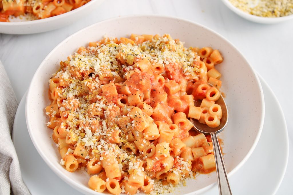 Front angle view on a white bowl that contains a vegan creamy tomato pasta. The dish is topped with a crispy cheesy panko topping and there is a spoon in the bowl as well. You can see another bowl of pasta in the background.