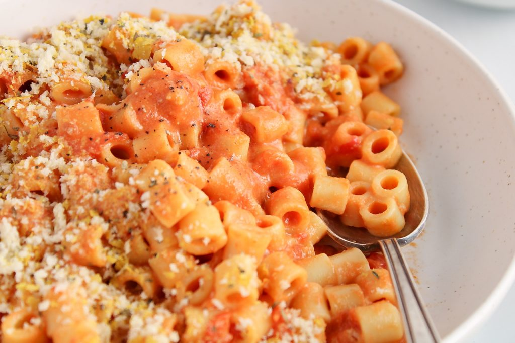 Close up on a bowl containing a vegan creamy tomato pasta with a spoon in the noodles as well.