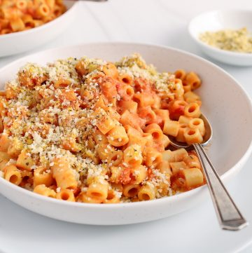 Close up on a bowl containing a vegan creamy tomato pasta with a spoon in the noodles as well. There is a second bowl of noodles in the background and a smaller bowl with more of the crispy panko cheesy topping.