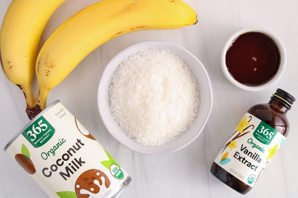 Showing are the ingredients needed to make this recipe: you can see a bowl filled with shredded coconut, bananas, a bottle of vanilla extract, a can of coconut milk and a small white bowl containing maple syrup.