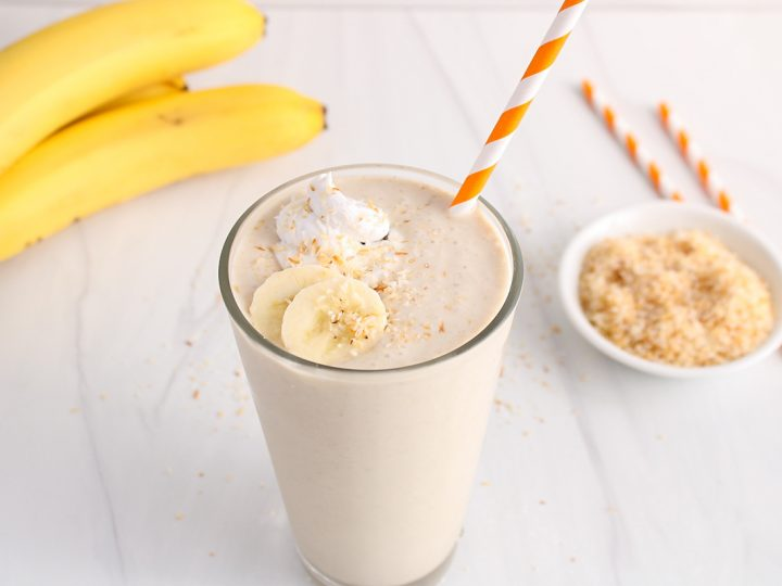 Showing is a tall glass that's filled with an homemade coconut milkshake. The glass is topped with sliced banana, coconut whipped cream and toasted shredded coconut. There is a orange straw in the glass as well as 2 more straws in the background. Also in the background, there is a small bowl containing some toasted shredded coconut with some fresh bananas.