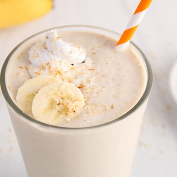 Close up on a glass that's filled with a homemade coconut milkshake. The glass is topped with coconut whipped cream, sliced bananas and toasted shredded coconut.