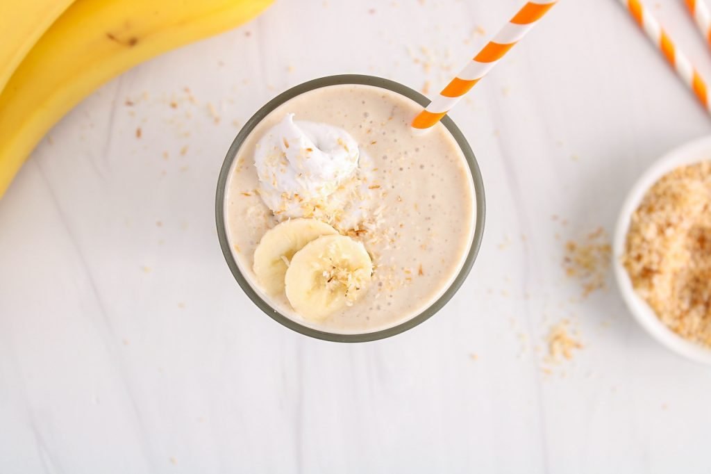 Overhead view on a glass filled with a no ice cream coconut milkshake that's topped with sliced bananas and toasted shredded coconut. There is an orange straw in the glass as well with a small bowl that contains some more toasted shredded coconut on the side.