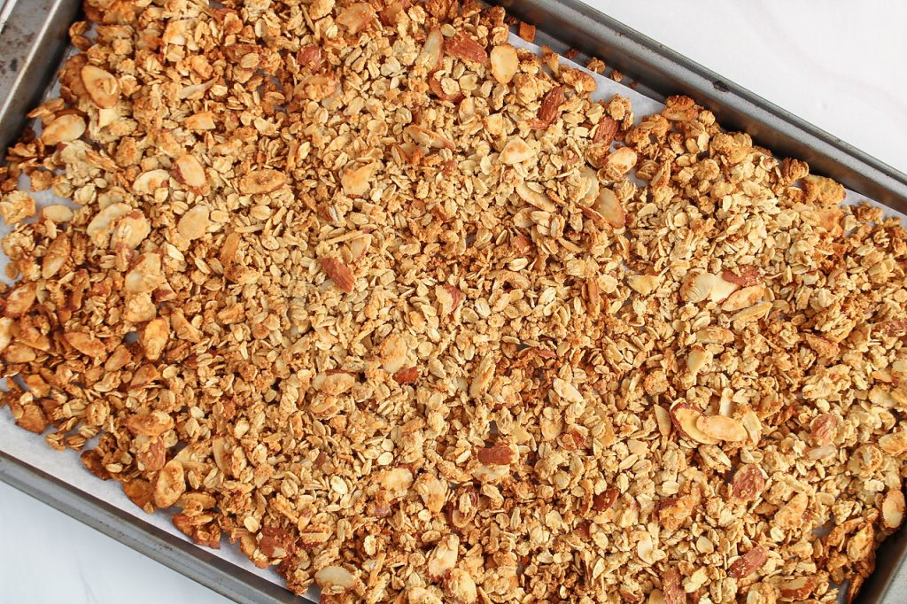 Showing is an overhead view on a baking sheet that contains a vanilla almond granola.