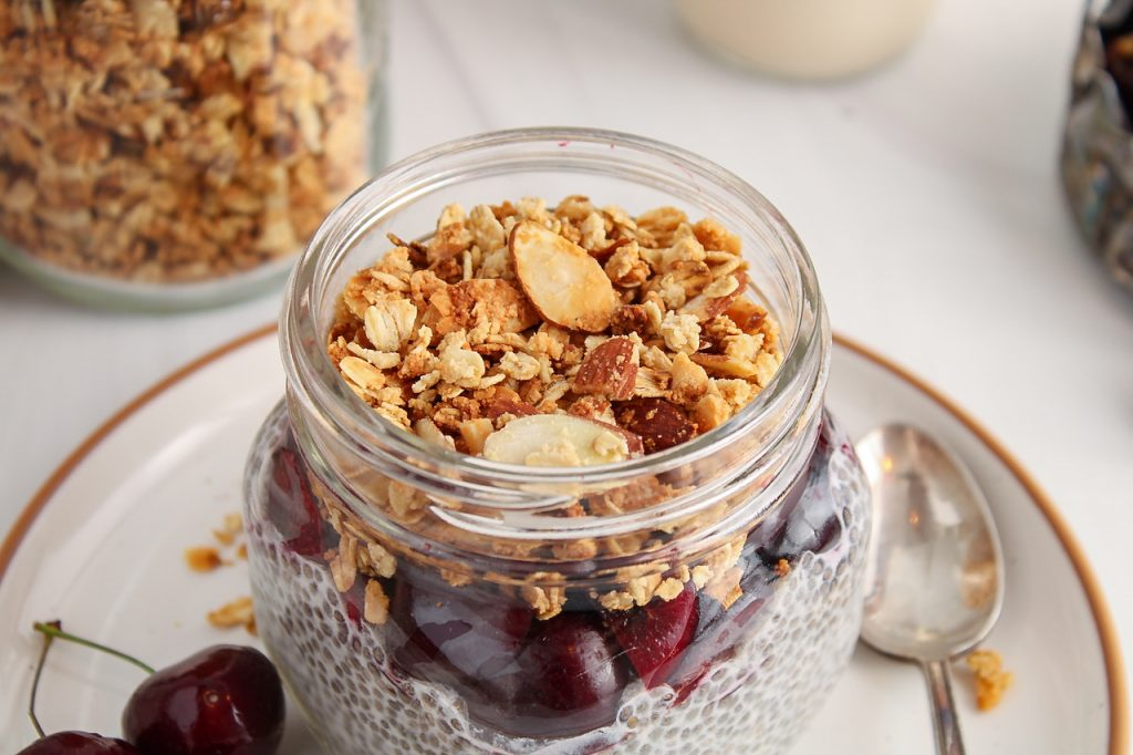Front angle view on a glass jar that layers a chia pudding, with chopped fresh cherries and topped with an homemade vanilla almond granola. You can see more granola in a big jar in the background as well as more cherries.