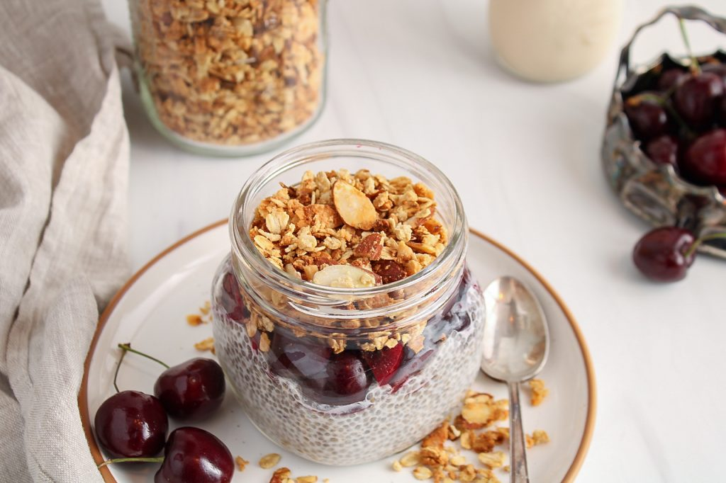 Front angle view on a glass jar that layers a chia pudding, with chopped fresh cherries and topped with an homemade vanilla almond granola. You can see more granola in a big jar in the background as well as more cherries and a beige hand towel.