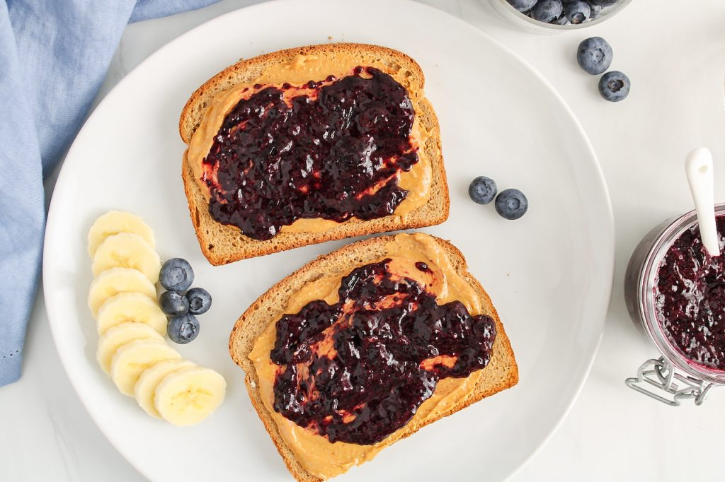 Over head view on 2 toasts that are on a white plate. The toasts are topped with peanut butter and a blueberry chia jam. There are sliced bananas and fresh blueberries on the plate as well. You can see a jar filled with homemade blueberry jam on the side of the plate.