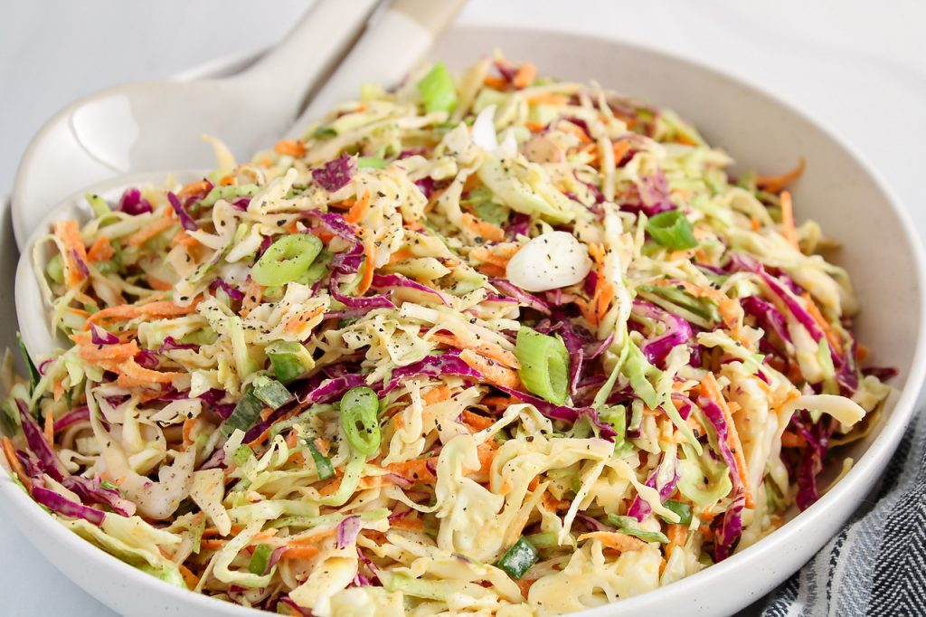 Close up on a large bowl filled with a homemade creamy vegan coleslaw.