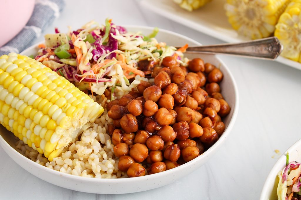 Front angle view on a bowl that's filled with brown rice, half of a corn on the cob, some creamy vegan coleslaw and some saucy BBQ Chickpeas.
