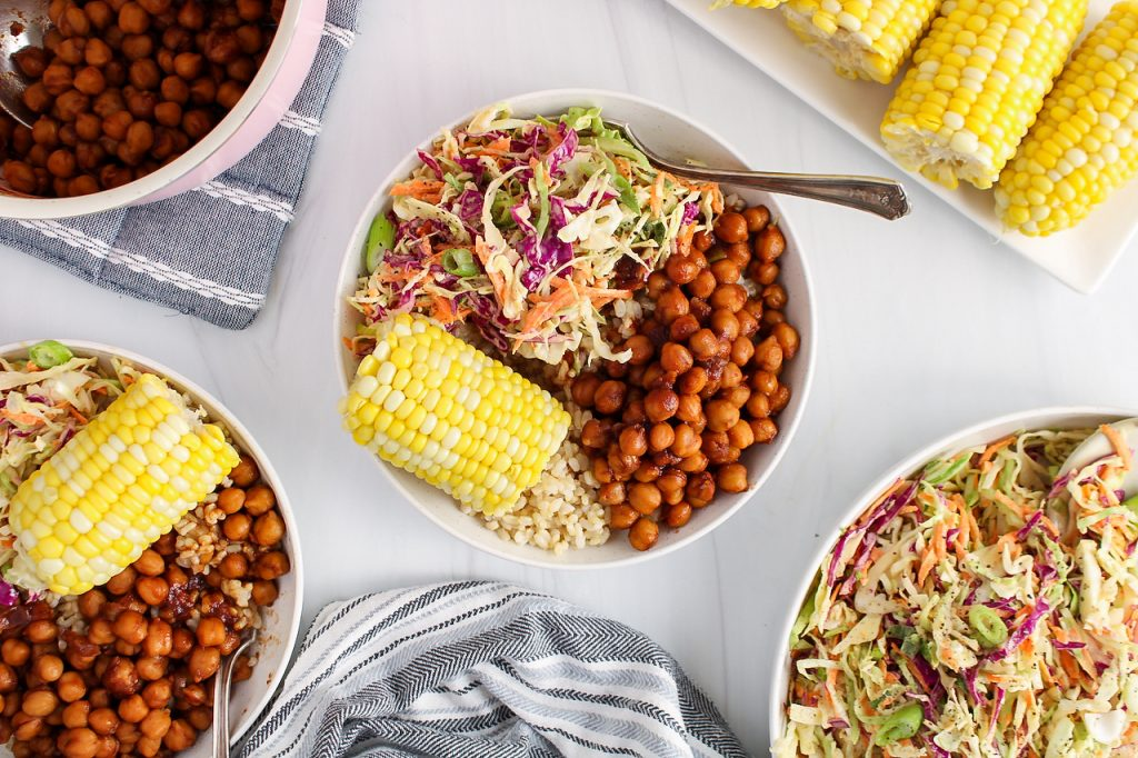 Overhead view on 2 bowls that contains brown rice, corn on the cob, a vegan creamy coleslaw and some BBQ chickpeas. There is a large bowl with more of the coleslaw on the side, more corn on the cob on a rectangular plate and the pot used to cook the BBQ chickpeas.