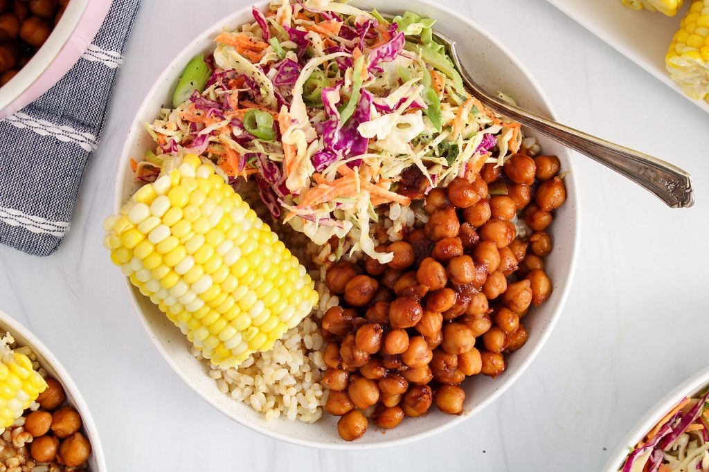 Overhead view on a bowl that contains brown rice, corn on the cob, a vegan creamy coleslaw and some BBQ chickpeas. There is a fork on the side of the plate.