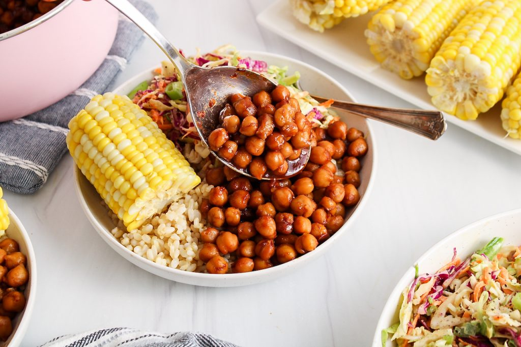 Front angle view on a bowl that contains brown rice, corn on the cob, a vegan creamy coleslaw and some BBQ chickpeas. There is a fork on the side of the plate and you can see a large serving spoon adding more BBQ chickpeas to the bowl. There are more corn on the cob in the background as well.