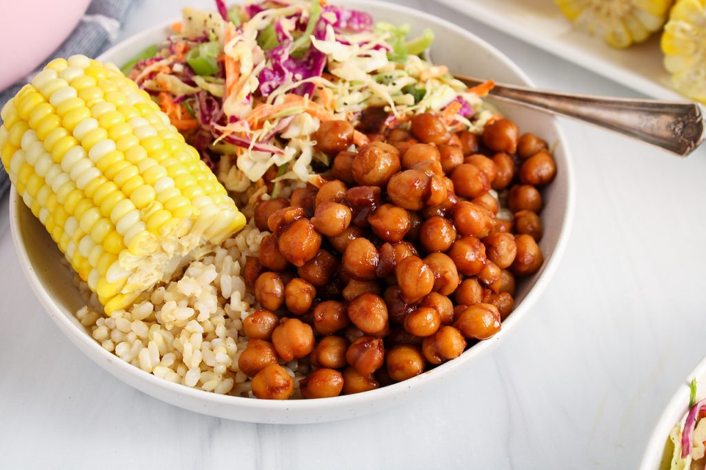 Front angle close up on a bowl that contains brown rice, corn on the cob, a vegan creamy coleslaw and some BBQ chickpeas. There is a fork on the side of the plate and you the focus is on the chickpeas to show their texture.