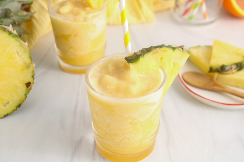 Front angle view on a short glass containing a homemade pineapple slush. There is a yellow straw in the glass and also a wedge of pineapple against the rime of the glass. You can see more glasses of the slush in the background as well as more straw and fresh fruits.
