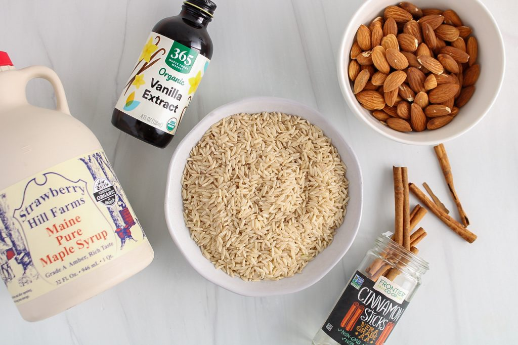 Ingredients needed to make this recipe. You can see a few bowls containing: brown rice, vanilla extract, cinnamon sticks, raw almonds and maple syrup.
