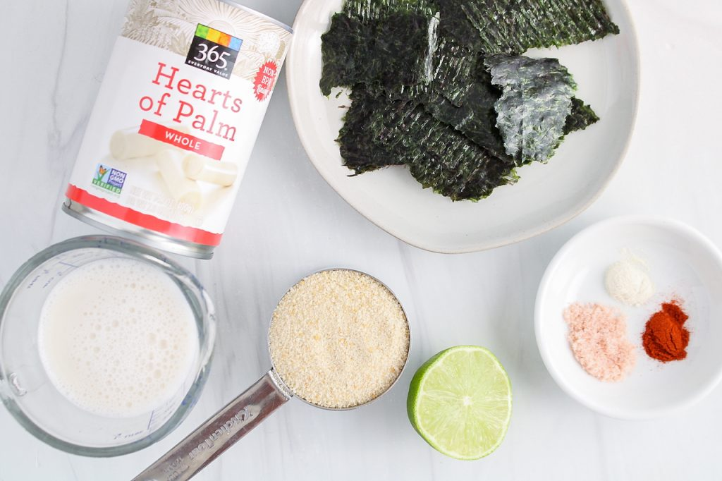 Showing are the ingredients needed to make the filling: hearts of palm, nori sheet, breadcrumbs, lime, salt, paprika, onion powder and vegan milk.