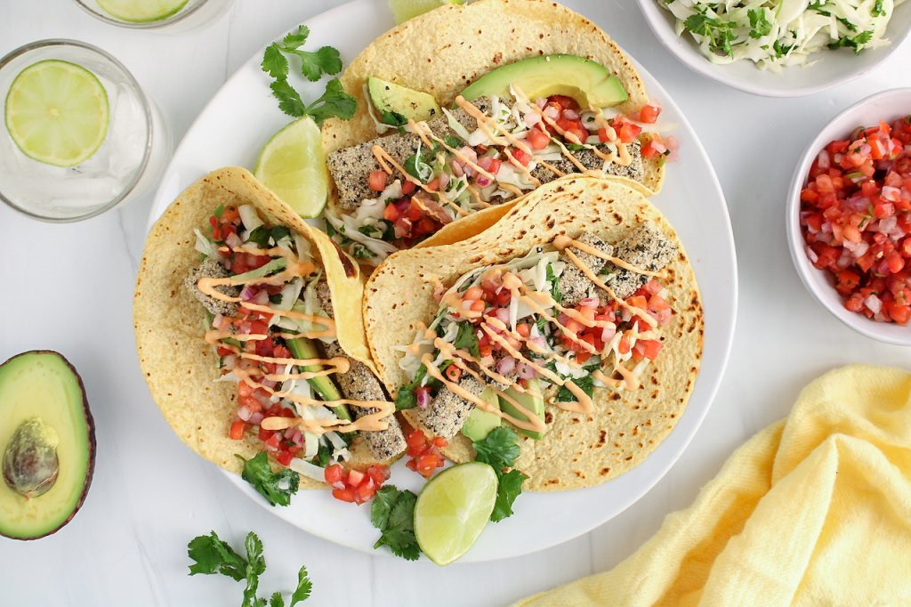 There are 3 vegan fish tacos that are on a white plate with small bowls around the plate containing some pico de gallo, lime slaw, half of an avocado, a yellow hand towel and 2 glasses of water with a lime wedge inside.
