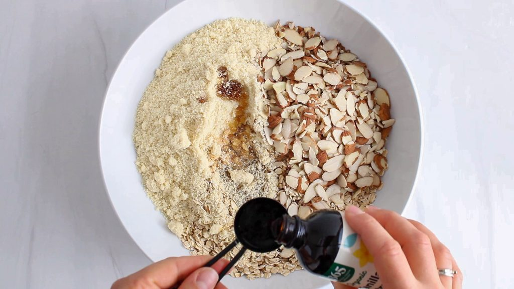 In process picture: you can see a white bowl that contains rolled oats, almond flour, slivered almonds and you can see hands pouring some vanilla extract into a tablespoon to add to the bowl.