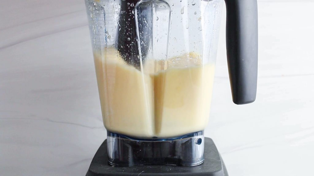 In process picture: you can see a blender that's blending a creamy yellow mixture.
