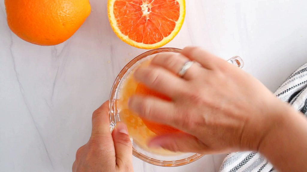 In process picture: you can see someone juicing some orange using a glass juicer.