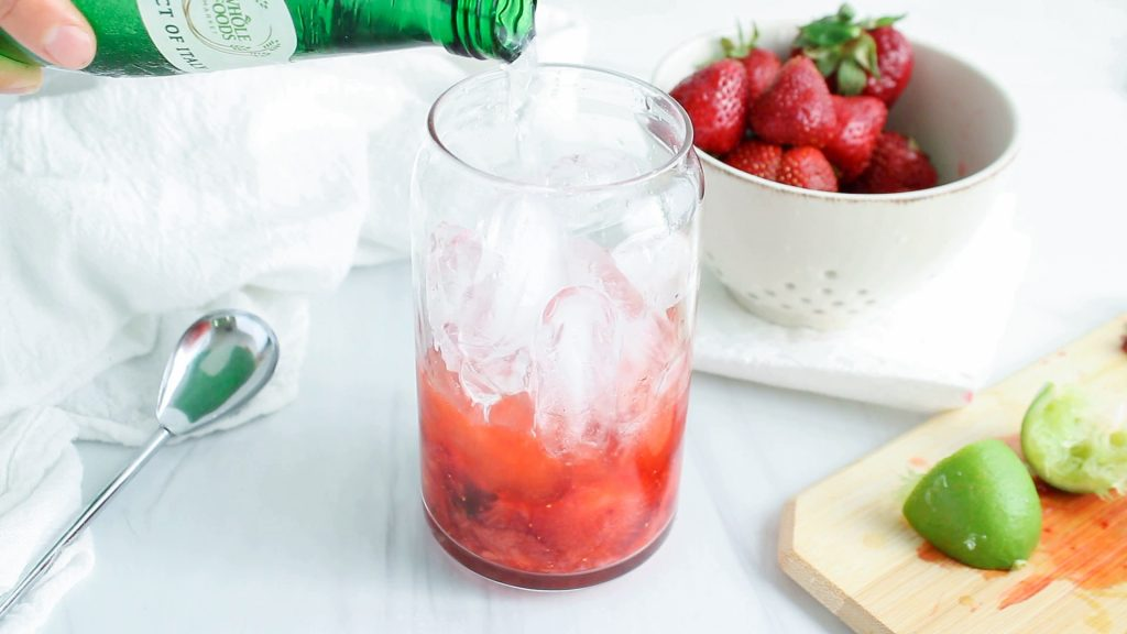 In process picture: showing is a front view on a tall glass that contains fresh strawberries, fresh mint and lime juice that were muddled together and you can see a hand pouring some sparkling water over.