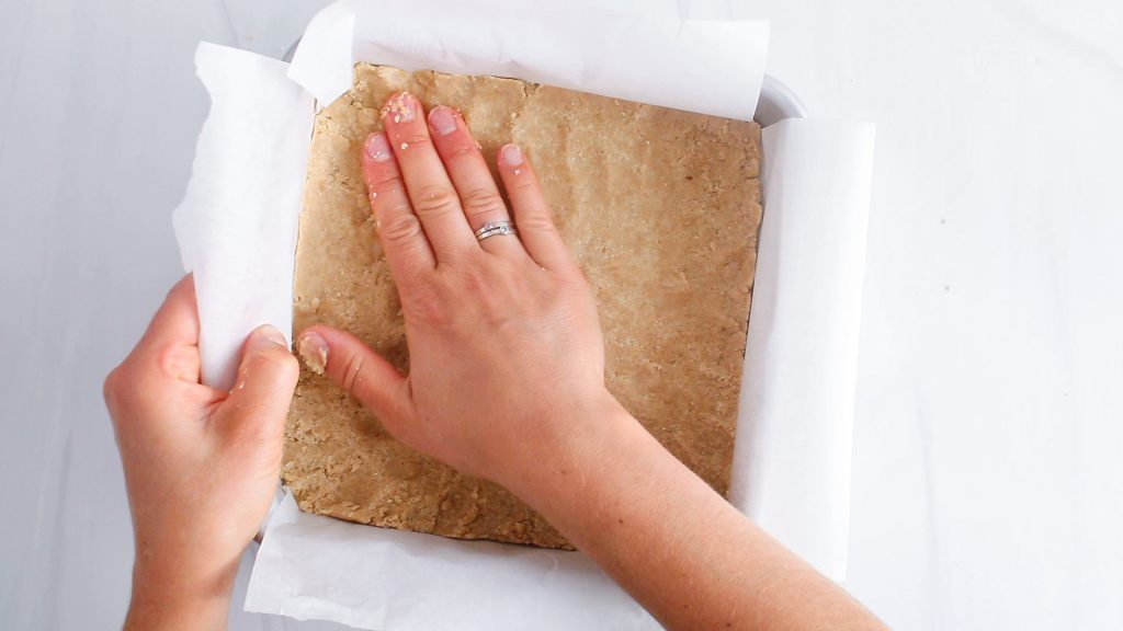 In process picture: you can see a hand pressing on a flour mixture at the bottom of a square dish.