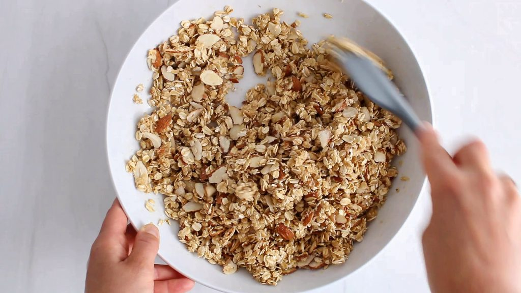 In process picture: you can see hands stirring in a bowl a rolled oat mixture with a spatula.