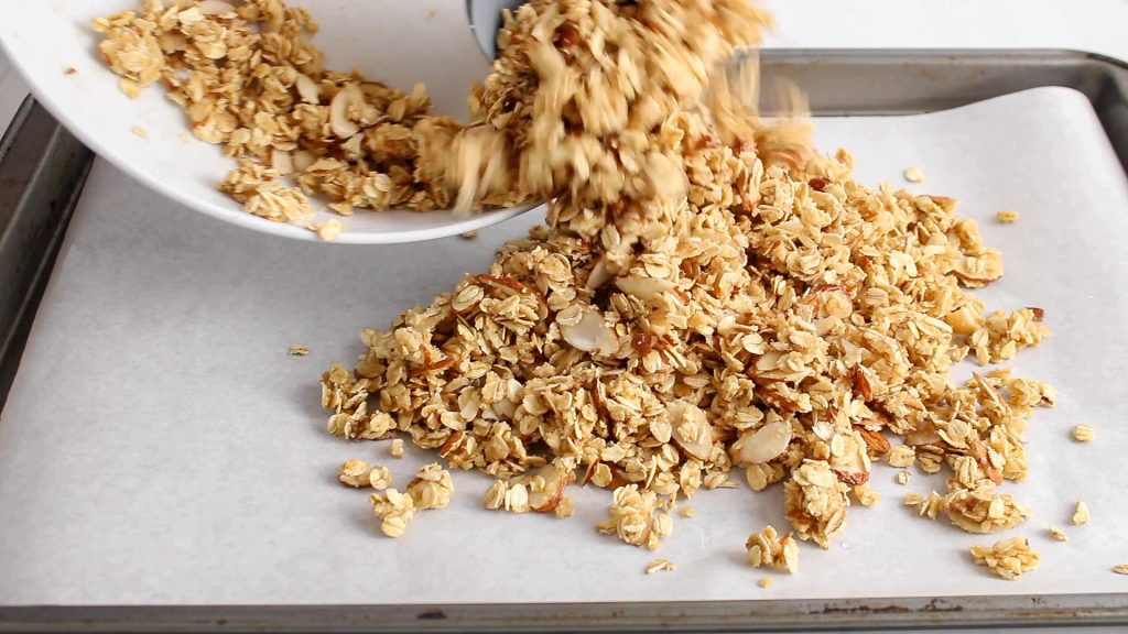 In process picture: there is an oat mixture being pouring over a baking sheet to bake in the oven.