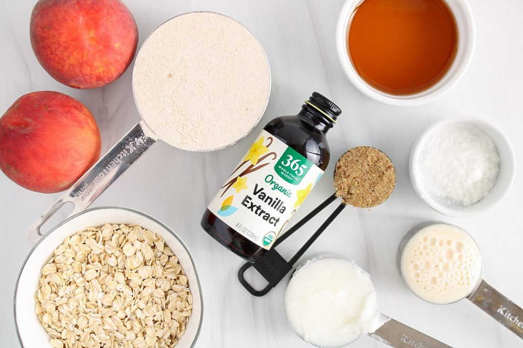 Showing are the ingredients needed to make this recipe: you can see small bowls containing rolled oats, flour, fruits, maple syrup, coconut oil, vegan milk, baking powder, vanilla extract and flax seed (ground).