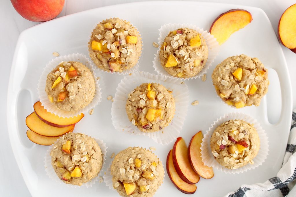 Overhead view on a large rectangular white plate that contains a few vegan peach muffins. There are some sliced peaches surrounding the muffins as well.