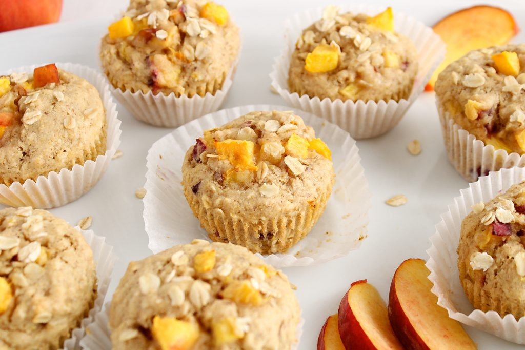 Front angle view on a vegan peach muffin that on a large white plate. The muffin still is on its muffin tin and there are more muffins around as well as a few slices of peach.