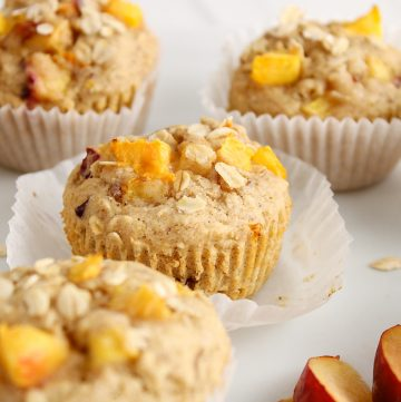 Front angle view (close up) on a vegan peach muffin that on a large white plate. The muffin still is on its muffin tin and there are more muffins around as well as a few slices of peach.