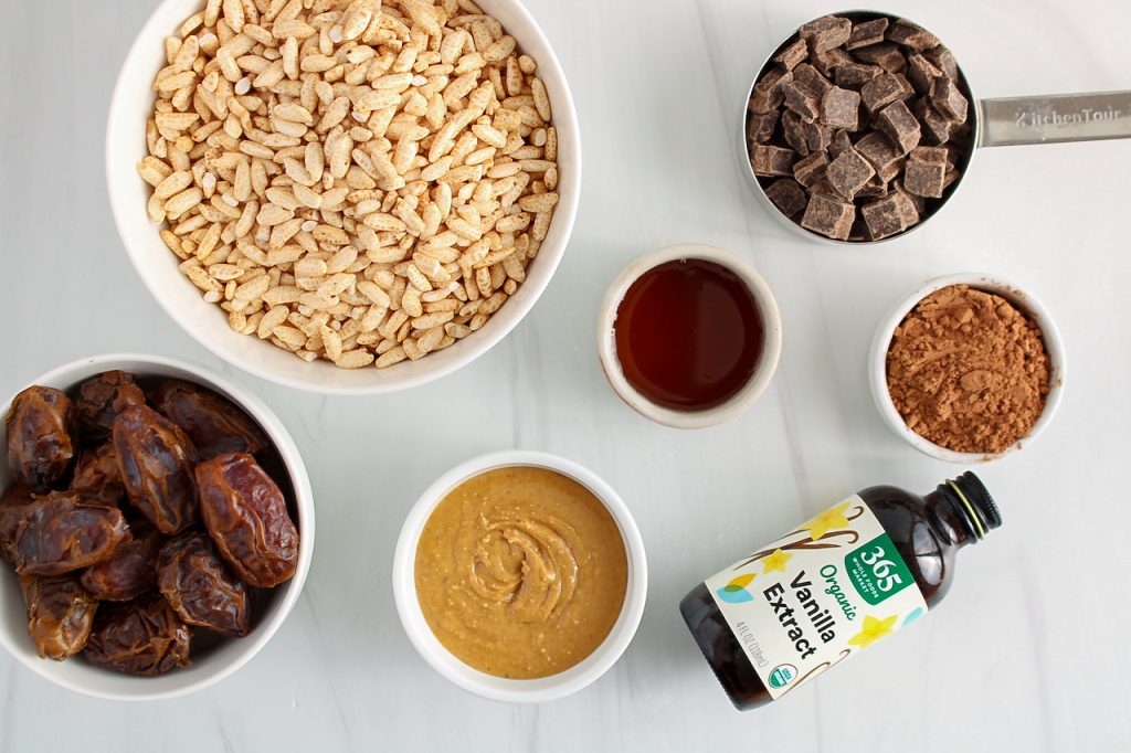 Showing are the ingredients needed to make this recipe: there are a few bowls containing puffed brown rice, fresh medjool dates, dark chocolate chips, maple syrup, vanilla extract, cacao powder and peanut butter.