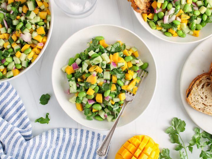 Overhead view on 2 bowls that contains a cucumber mango salad. There is a fork in one of the bowl and you can see a larger serving bowl with more of the salad. Also on the side on the table, there is a blue and white hand towel, a cut mango, fresh cilantro and a plate with crusty bread.