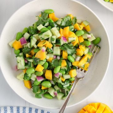 Overhead view on a bowl that contains a cucumber mango salad. There is a fork on the side of the bowl and pieces of a fresh mango and cilantro on the side as well.