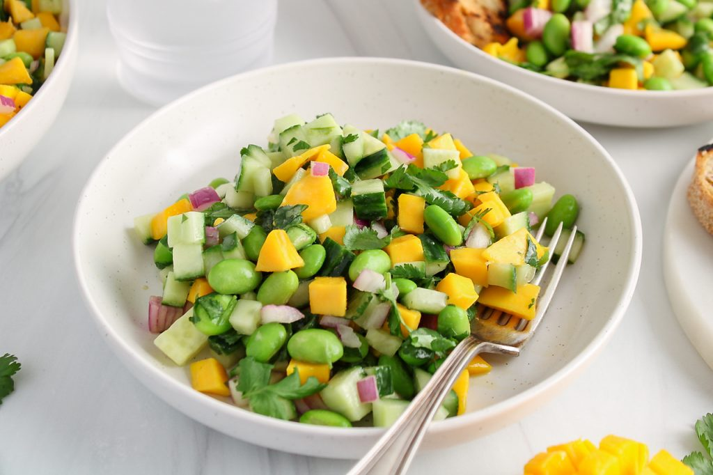Front angle view on a bowl filled with a cucumber mango salad that's also filled with edamame. The bowl has a fork on the side and you can see some bread in the background as well.