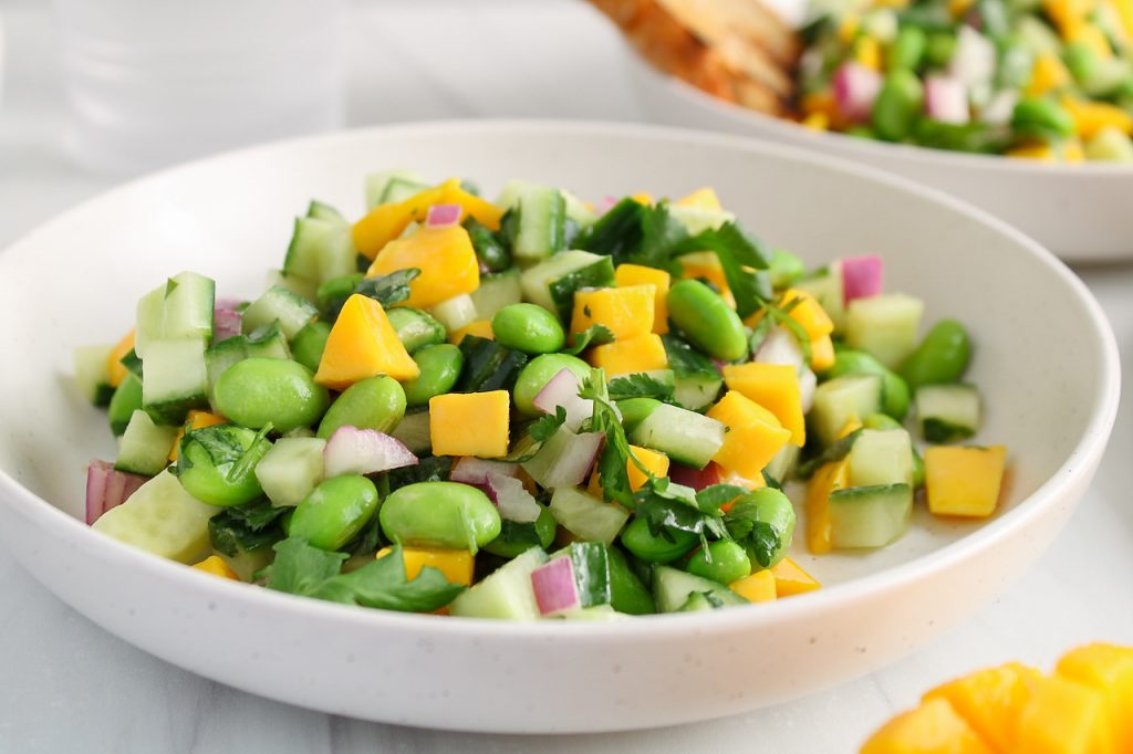 Front angle view on a bowl filled with a cucumber mango salad that's also filled with edamame. The bowl has a fork on the side and you can see a mango that's diced in the background as well as a second bowl with some of the salad.