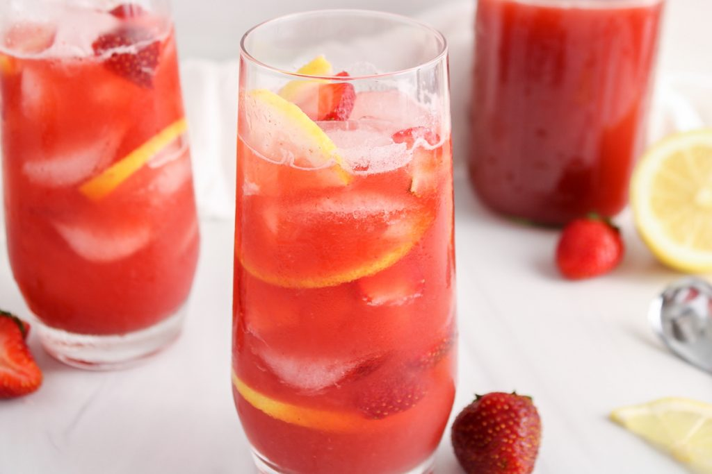 Front view on a tall glass filled with a strawberry acai lemonade refresher. You can see fresh strawberries, ice cubes and lemon slices within the lemonade. There is also a second glass of lemonade in the background as well as a larger pitcher with more of it.