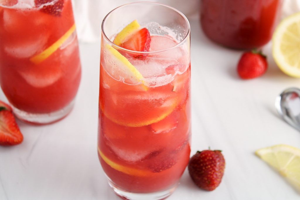 Angle view on a tall glass filled with a strawberry acai lemonade refresher. You can see fresh strawberries, ice cubes and lemon slices within the lemonade. There is also a second glass of lemonade in the background as well as a larger pitcher that contains more of the lemonade and some fresh fruits on the table too.