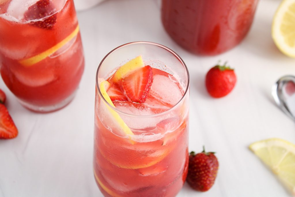 Front view with an angle in a glass of strawberry acai lemonade refresher. There are fresh fruits in the background, and more of the lemonade in a larger pitcher and a second glass with some of it too. There are some ice cubes and sliced strawberries inside the glass as well.