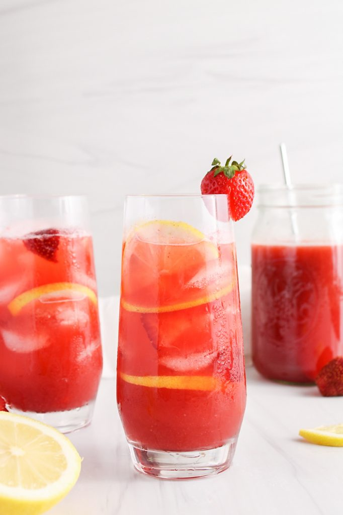 Long vertical picture on a tall glass filled with a strawberry acai lemonade refresher. You can see fresh strawberries, ice cubes and lemon slices within the lemonade. There is also a second glass of lemonade in the background as well as a larger pitcher with more of it.